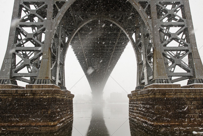 Low angle view of Williamsburg Bridge over river in foggy weather