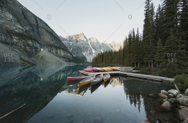 Boats on pier at calm lake by mountains