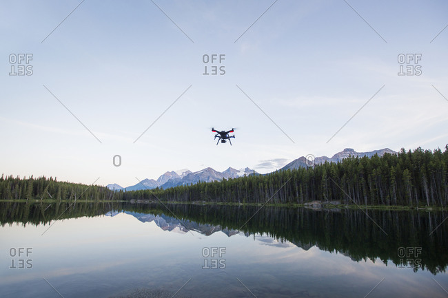 Octocopter flying over reflection lake by forest against sky