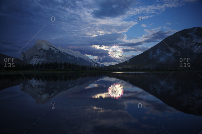 Reflection of fireworks display and mountains in lake at night