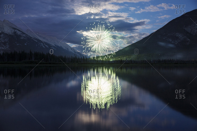 Reflection of fireworks display and mountains in lake