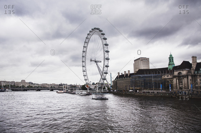 Millennium Wheel by Thames River against cloudy sky