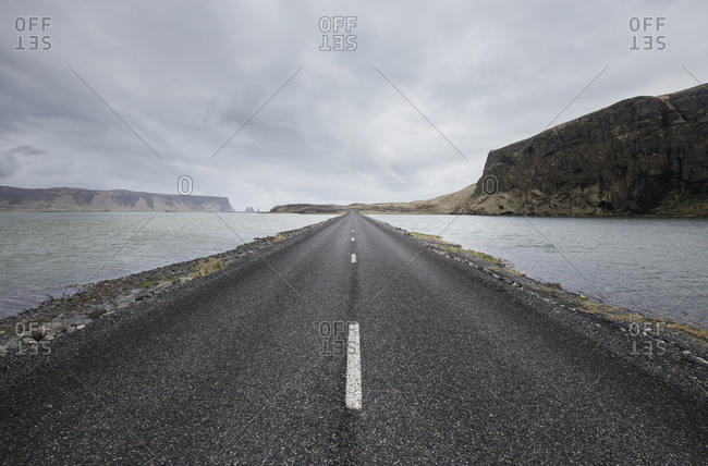 Road amidst sea against cloudy sky
