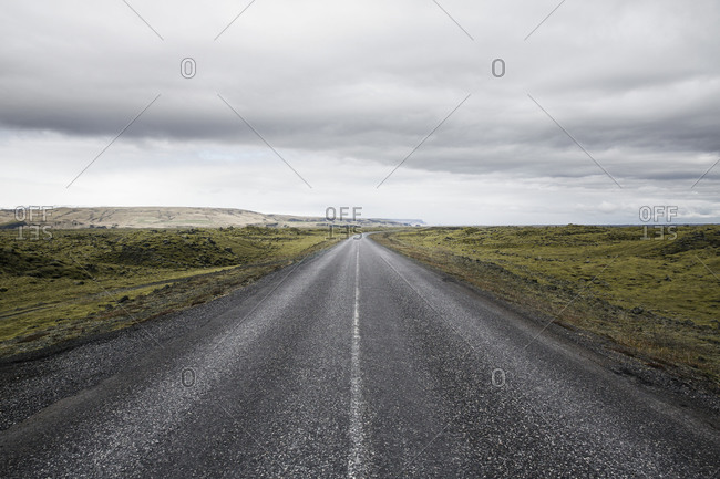 Country road passing amidst green landscape against cloudy sky