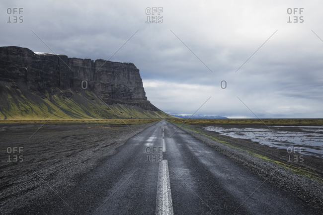 Road leading towards cliff against cloudy sky