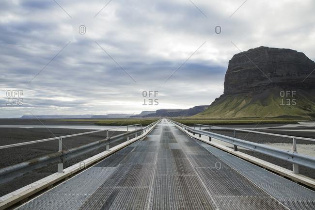 Footbridge leading towards cliff against cloudy sky