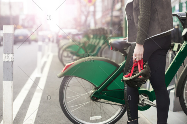 Midsection of woman standing by bike on sidewalk