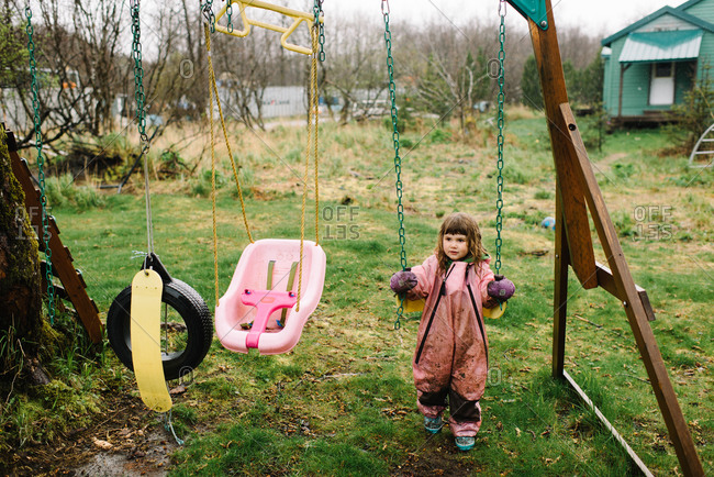 Toddler girl playing on a swing set