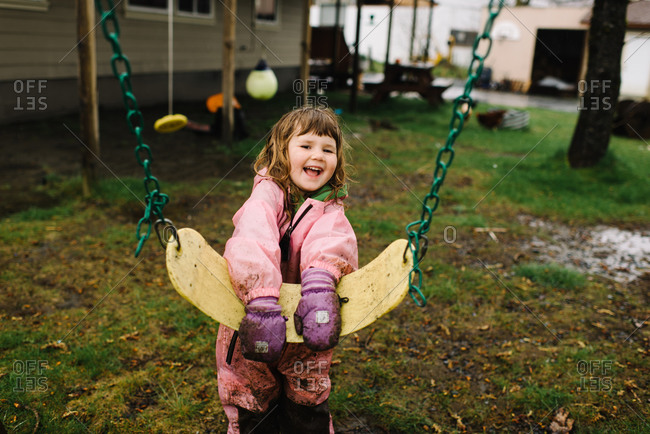 Smiling toddler girl playing on a swing