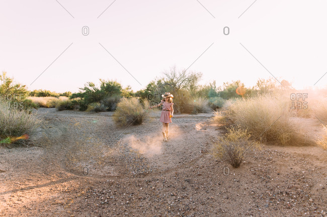 Girl holding a grapefruit and playing in a desert