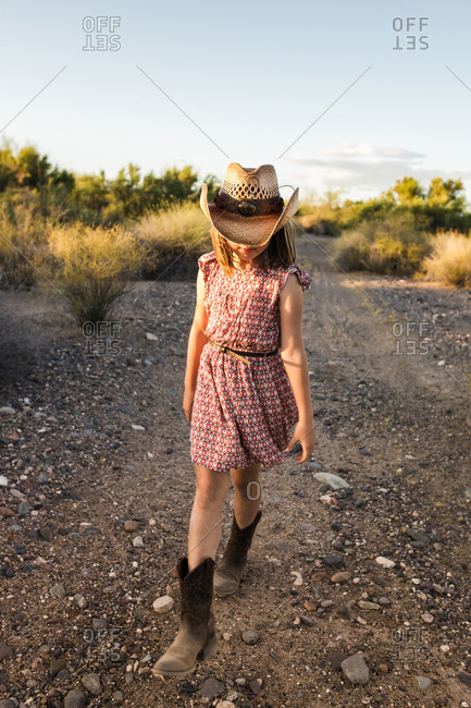 Little girl walking on a dirt trail in the desert