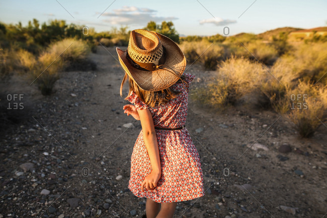 Girl in a cowgirl hat skipping on a trail in the desert