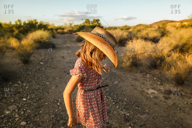 Girl in a cowgirl hat standing on a trail in the desert