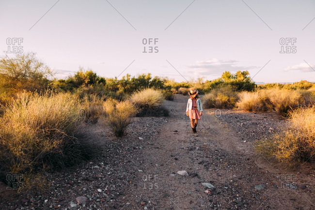 Girl in a cowboy hat walking on a dirt path in the desert