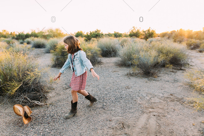 Girl chasing a cowboy hat in the desert