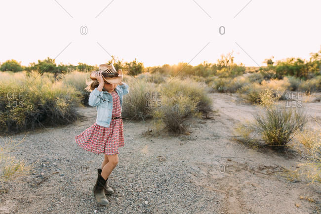 Little girl standing in a desert putting on a cowgirl hat