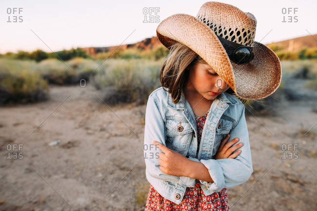 Girl in a cowboy hat standing in the desert