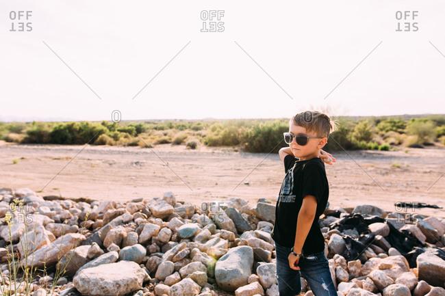 Little boy throwing rocks in the desert