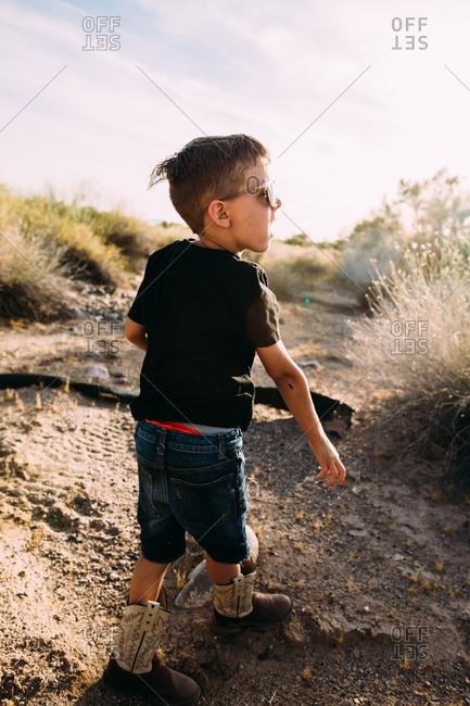 Stylish little boy walking in the desert