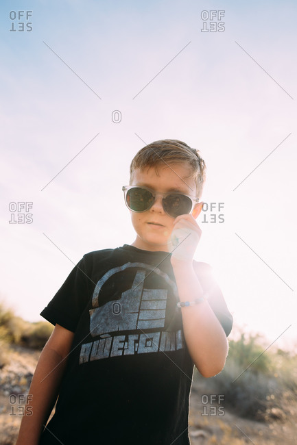 Stylish boy standing in the desert putting on his sunglasses