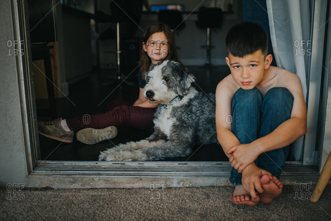 Brother and sister sitting at an open patio door with their dog