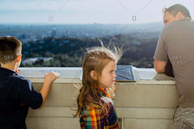 Father and his two children standing on a balcony overlooking a city