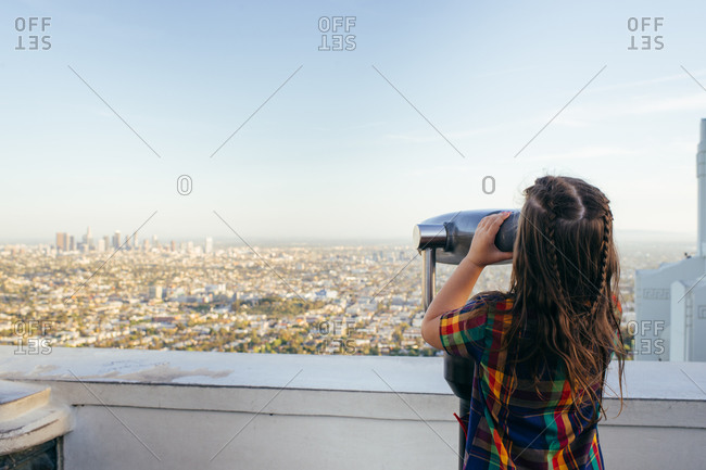 Little girl looking at a cityscape from a viewfinder at an observation point