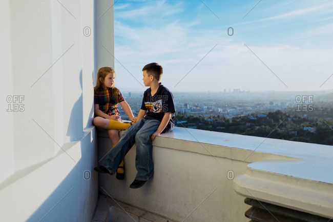 Brother and sister sitting on a balcony ledge overlooking a vast city