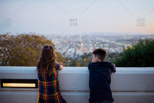 Brother and sister on a balcony overlooking a city at dusk