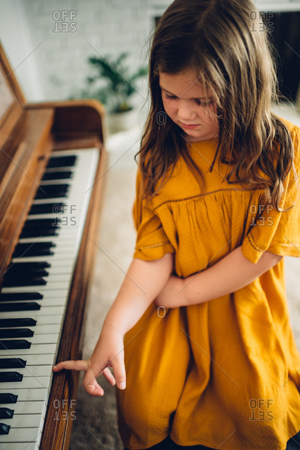 Little girl pressing a key on a piano