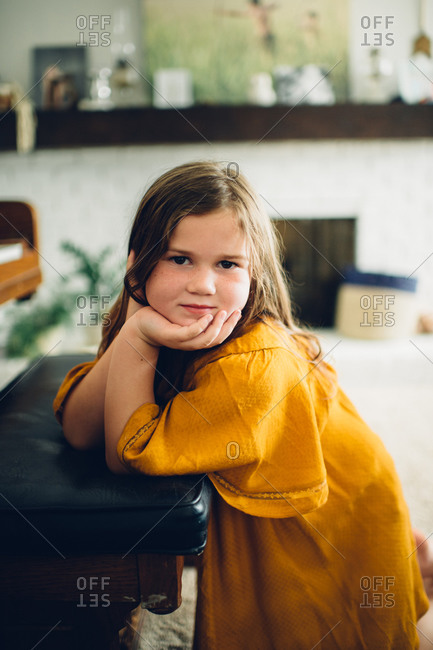 Little girl propping herself on a piano bench