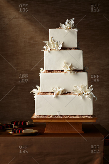 A square four tiered cake next to slices of cake