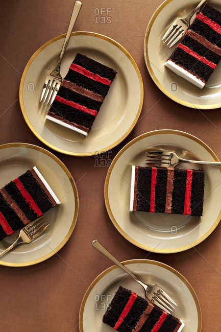 Slices of layered cake on gold trim plates