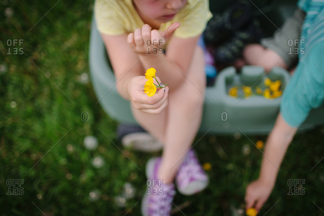 Children sitting in a green wagon holding yellow flowers