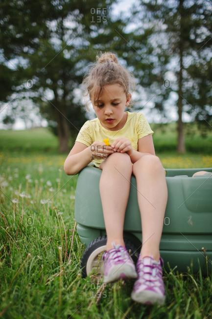 Little girl sitting in a green wagon