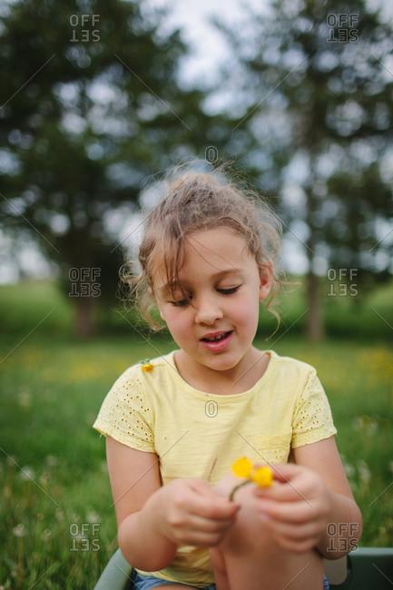 Little girl holding yellow wild flowers
