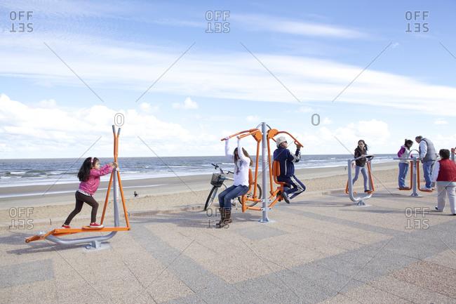 Carrasco, Uruguay - March 16, 2013: People using beach workout equipment at Carrasco, Uruguay