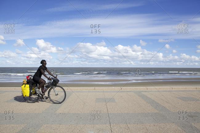 Carrasco, Uruguay - March 16, 2013: Woman riding bike next to beach in Carrasco, Uruguay