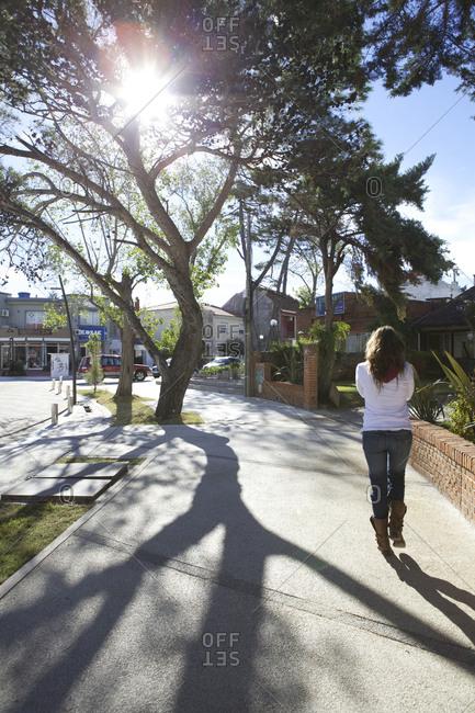 Carrasco, Uruguay - March 16, 2013: Woman walking on the sidewalk of Carrasco, Uruguay