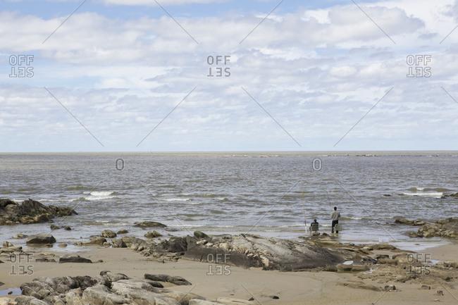 Two men fishing at Carrasco beach, Uruguay