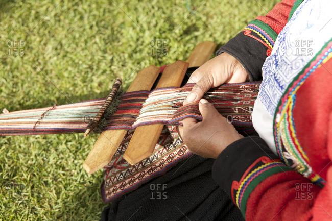 Close up of woman weaving a textile in Chinchero, Peru_