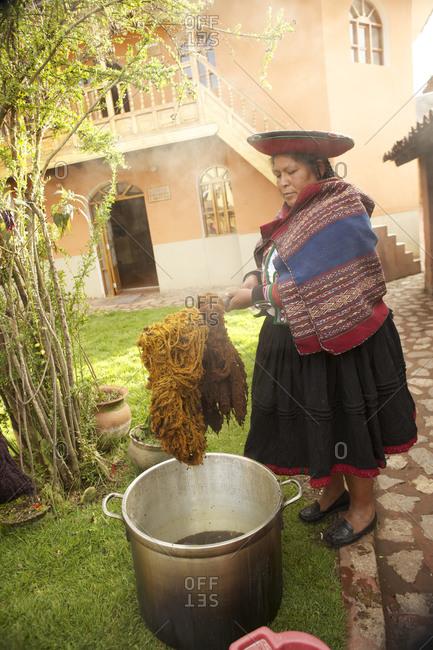 Chinchero, Peru - April 4, 2013: Woman dying yarn
