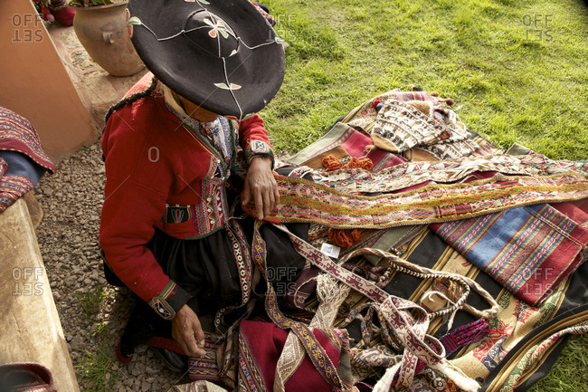 Woman arranging various textiles on a blanket