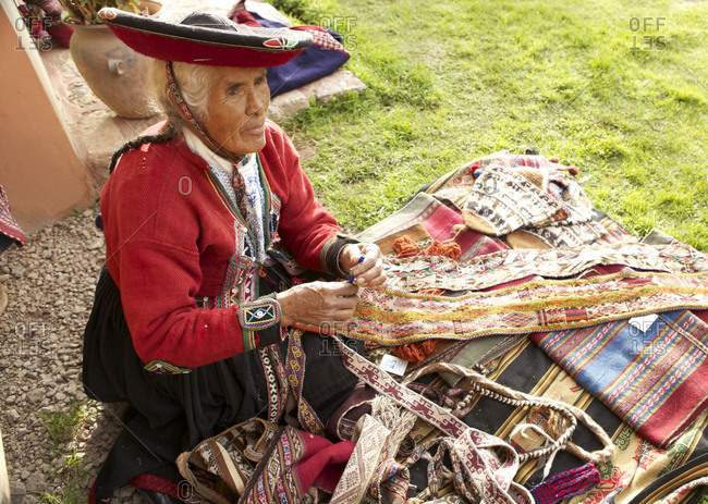Chinchero, Peru - April 4, 2013: Woman sitting next to a blanket with various textiles