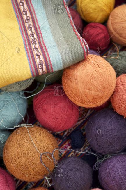Balls of various color thread next to a handmade textile