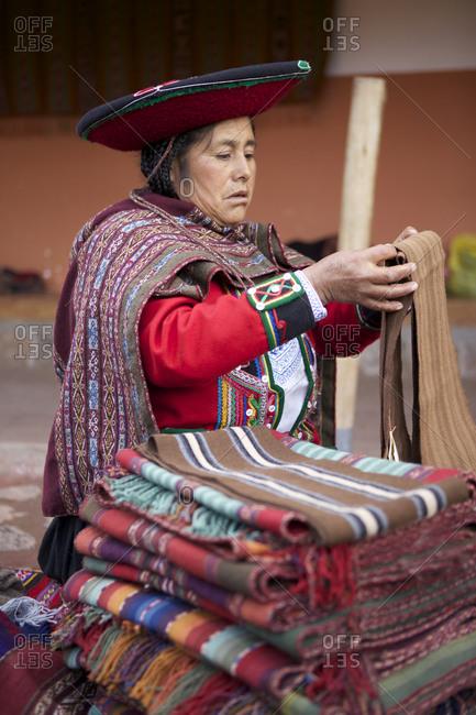 Chinchero, Peru - April 4, 2013: Woman folding and stacking colorful textiles