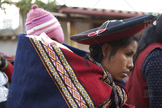 Chinchero, Peru - April 4, 2013: Woman carrying baby on back