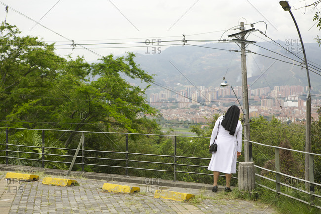 Nun looking at view of a town in a distance, Medellin, Colombia
