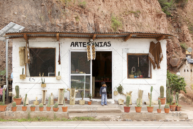 Salta, Argentina - February 2, 2016: A boy standing at the doorway of a handicraft storefront in Cuesta del Obispo, Argentina