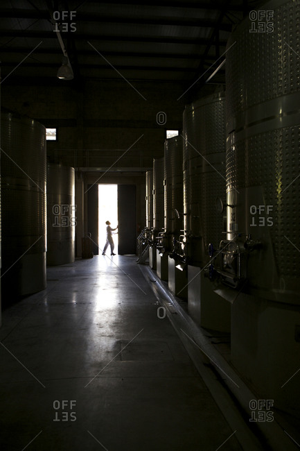 Colome Salta, Argentina - February 3, 2016: Man closing door to building with steel tanks for wine making, Colome, Argentina
